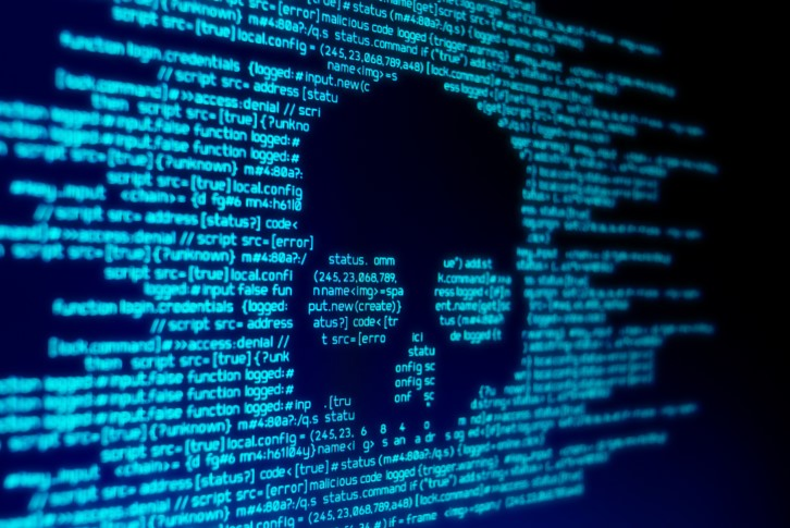 close up of malware on screen with skull shape among written code