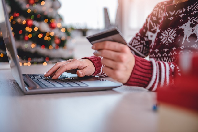 Woman in red Christmas jumper shopping on laptop with credit card. Online security concept for Intersys