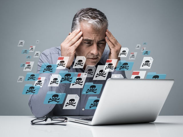 Businessman working with a computer full of viruses. He is frustrated with head in hands. Malware concept Intersys Ltd