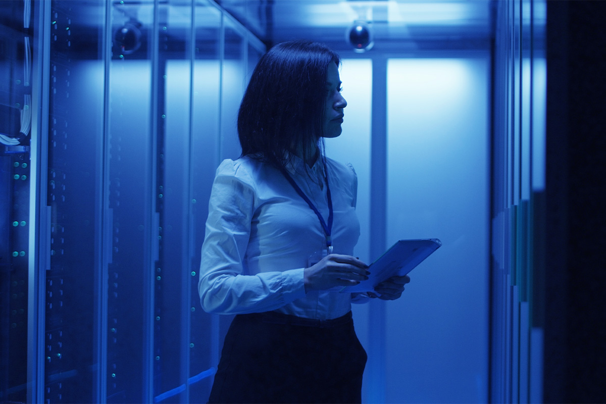 A female employee with a clipboard checks a server bank, as part of our cyber security audit services.