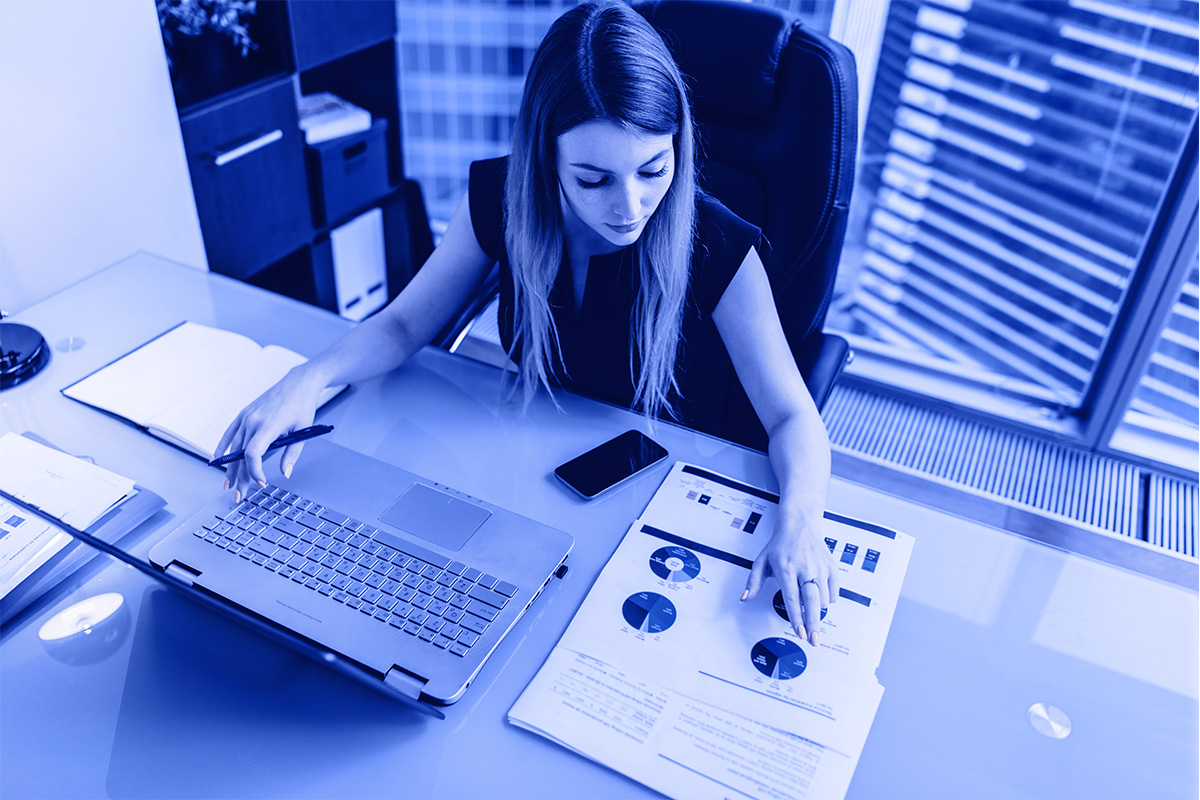 Woman at desk, with keyboard and chart using IT support for financial services.