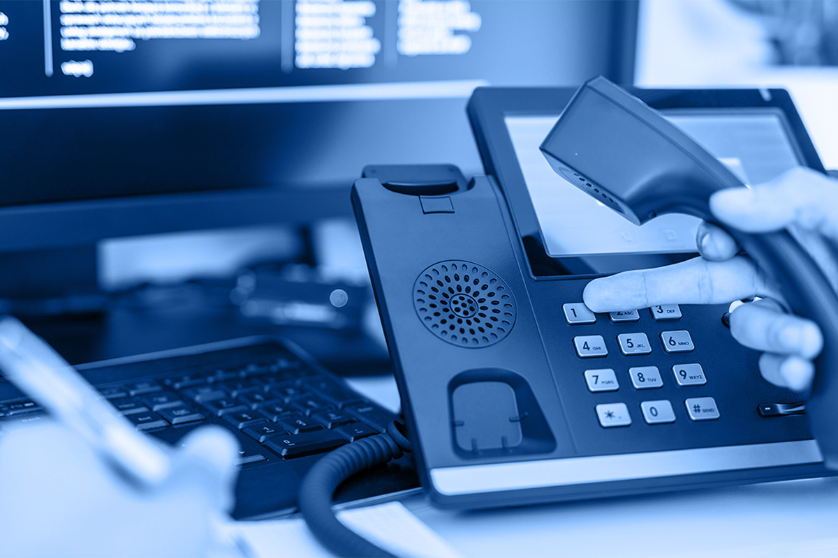 Hand dialling phone number on a console, to represent fully managed Office 365 support services from Intersys.