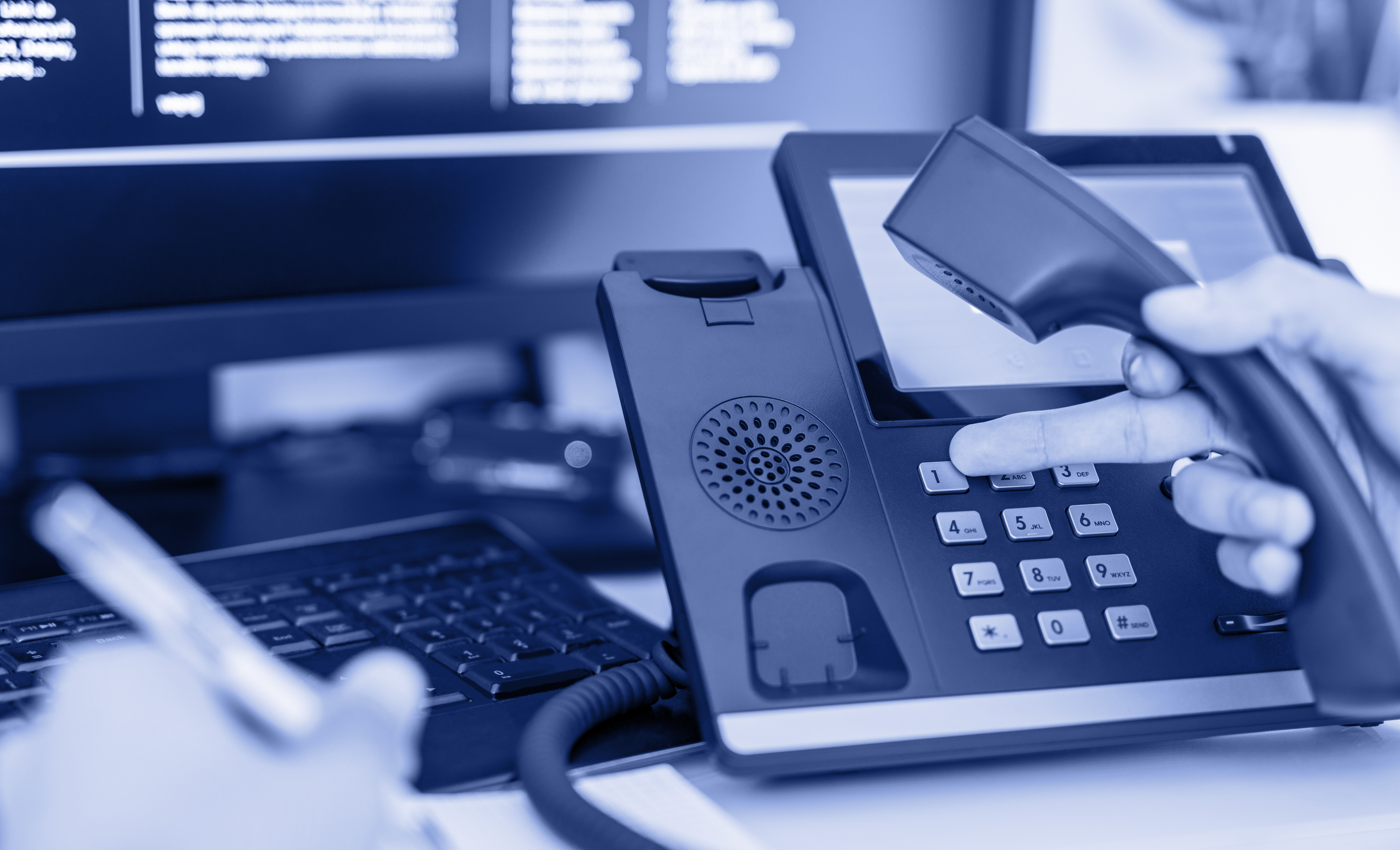 A hand dials on a telephone console, contacting Intersys for IT training services.