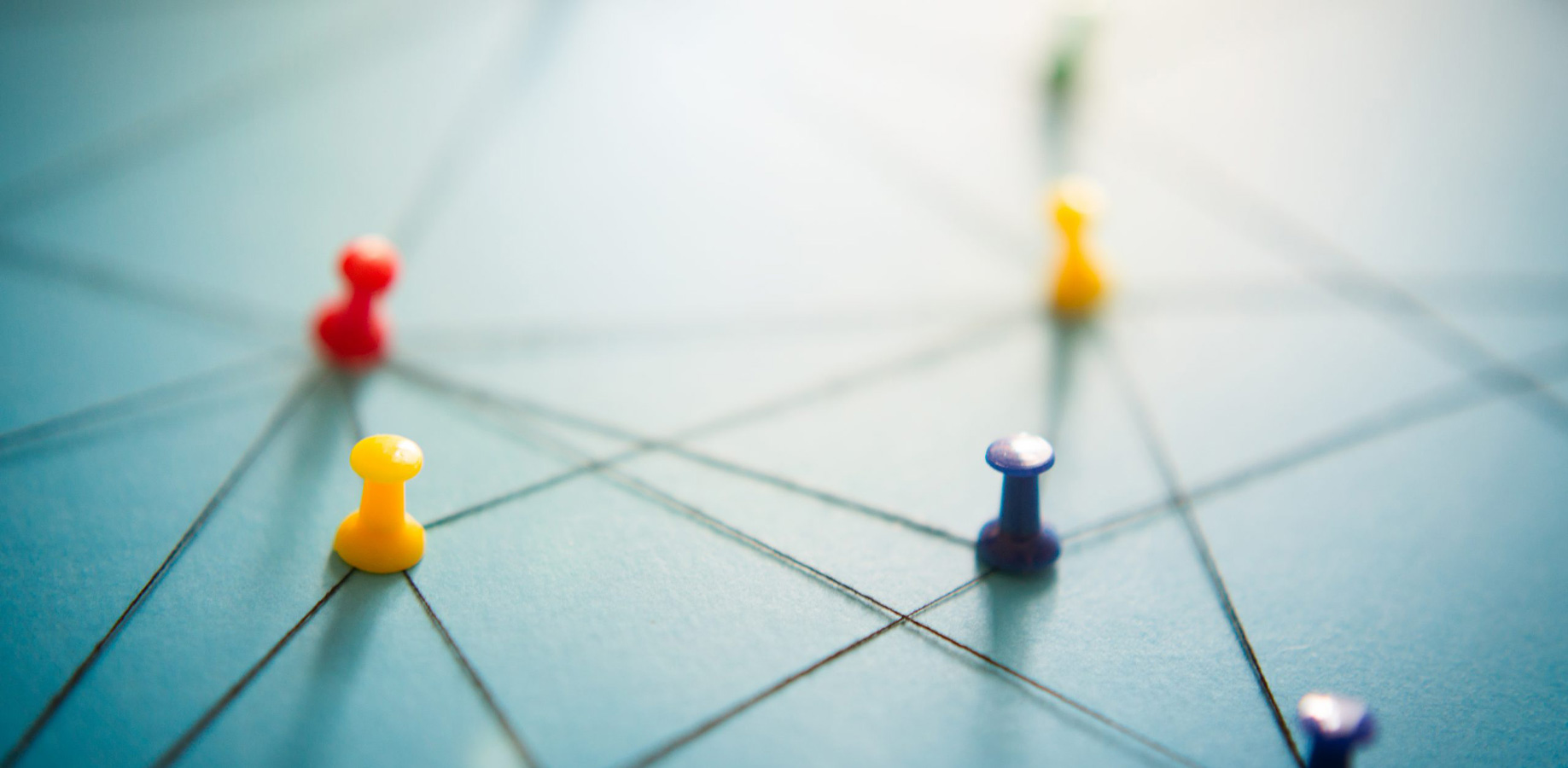 Coloured pins holding a web of interconnected string, to represent IT consultancy services strategy.